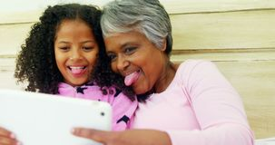 Grandmother and granddaughter using digital tablet in bed room 4k. Grandmother and granddaughter using digital tablet in bed room at home 4k stock video footage