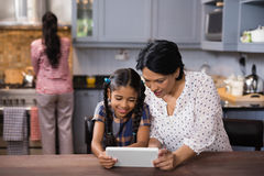 Grandmother and granddaughter using digital tablet in kitchen Royalty Free Stock Photo