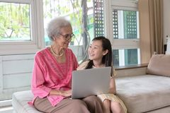 Grandmother and granddaughter using laptop computer and sitting. On sofa at home royalty free stock photography