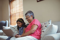 Grandmother and granddaughter using laptop in living room Stock Photos
