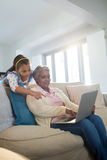 Grandmother and granddaughter using laptop in living room Stock Images