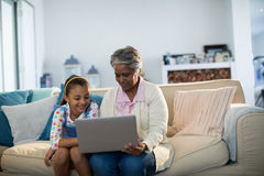 Grandmother and granddaughter using laptop in living room Stock Image