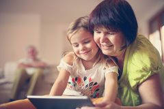 Grandmother and granddaughter using tablet. Grandmother and granddaughter laying on the floor and using tablet Royalty Free Stock Images