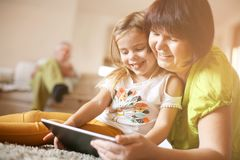 Grandmother and granddaughter using tablet. Grandmother and granddaughter laying on the floor and using tablet. Close up image Royalty Free Stock Image