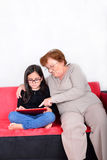 Grandmother and granddaughter using Tablet PC Stock Images