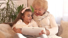 Grandmother and granddaughter using Tablet PC stock video