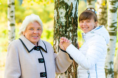 Grandmother and granddaughter walking in the park. Grandmother and granddaughter walking in the autumn park Stock Photography