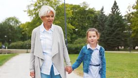 Grandmother and granddaughter walking at park stock video footage