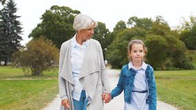 Grandmother and granddaughter walking at park stock video