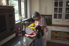 Grandmother and granddaughter washing utensil in kitchen sink Royalty Free Stock Photography