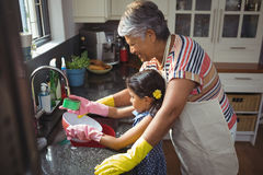 Grandmother and granddaughter washing utensil in kitchen sink Royalty Free Stock Images