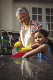Grandmother and granddaughter washing utensil in kitchen sink Royalty Free Stock Photos