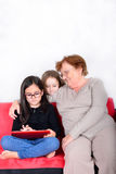 Grandmother and granddaughters using Tablet PC Stock Photo