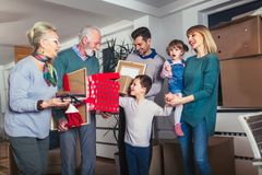 Grandmother and grandfather bring a gift for moving into a new apartment to their children. And having fun royalty free stock images