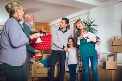Grandmother and grandfather bring a gift for moving into a new apartment to children. Grandmother and grandfather bring a gift for moving into a new apartment to royalty free stock photos