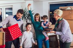Grandparents bring a gift for moving into a new apartment to their children. Grandmother and grandfather bring a gift for moving into a new apartment to their royalty free stock photo