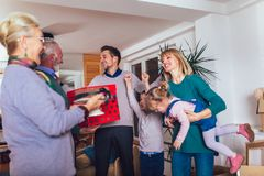 Grandparents bring a gift for moving into a new apartment to their children. Grandmother and grandfather bring a gift for moving into a new apartment to their stock photography