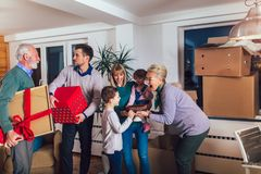 Grandparents bring a gift for moving into a new apartment to their children. Grandmother and grandfather bring a gift for moving into a new apartment to their stock photo