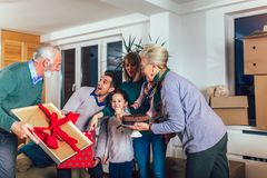 Grandparents bring a gift for moving into a new apartment to their children. Grandmother and grandfather bring a gift for moving into a new apartment to their royalty free stock photography