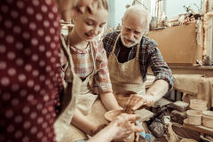 Grandmother and grandfather with granddaughter making pottery. At workshop Stock Photography