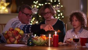 Grandmother, grandfather and grandson. Christmas dinner in the family, Thanksgiving. The family gathered around the set. Table, the evening was dark, the stock video footage