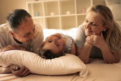 Grandmother and grandfather lie together with their granddaughter. stock images