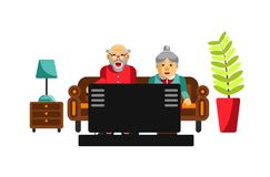 Grandmother and grandfather watching tv on the sofa. Elderly people. Entertain at home. Grandparents in front of tele in the living room. Plant in pot and lamp Royalty Free Stock Images