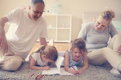 Grandparents help their granddaughters to write home. royalty free stock photo