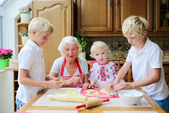 Grandmother with grandkids cooking in the kitchen. Loving caring grandmother, beautiful senior woman, baking tasty sweet cookies together with her grandchildren Stock Photo
