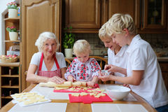 Grandmother with grandkids cooking in the kitchen. Loving caring grandmother, beautiful senior woman, baking tasty sweet cookies together with her grandchildren Stock Photos
