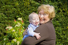 Grandmother with Grandson. Grandmother hugging happy grandson in sunny garden Royalty Free Stock Photography