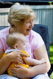 Grandmother with Grandson. Grandmother holding happy grandson in sunny garden Stock Photography