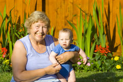 Grandmother with Grandson. Grandmother holding happy grandson in the garden Stock Photography