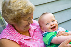 Grandmother with Grandson. Grandmother holding happy grandson in the garden Royalty Free Stock Image