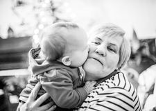 Grandmother and grandson baby kissing her. Grandmother with baby boy, happy love moment together, monochrome Stock Image
