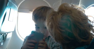 Grandmother and grandson with cell in the plane stock footage
