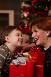 Grandmother and grandson at christmas. Portrait of happy grandmother and grandson looking to each other over christmas presents, smiling Stock Image