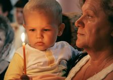Grandmother and grandson in church. KIVERCI, UKRAINE - 26 July 2009: Senior woman and little blond caucasian boy with candles in Orthodox Ukrainian Church Royalty Free Stock Photography