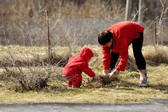 The grandmother and the grandson clean a site the village Stock Photo