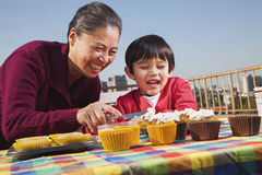 Grandmother and grandson decorating cupcakes Stock Photography
