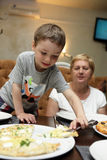 Grandmother and grandson eating pizza royalty free stock photography