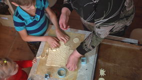 Grandmother with grandson and granddaughter make cookies on the kitchen table. stock video footage