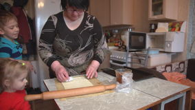 Grandmother with grandson and granddaughter make cookies on the kitchen table. stock video