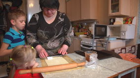 Grandmother with grandson and granddaughter make cookies on the kitchen table. stock footage