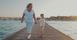 Grandmother and grandson having outdoor walk on. Steadicam shot of a grandmother walking with little grandchild along the wooden pier on resort. They holding stock video footage