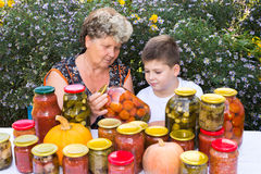 Grandmother with  grandson and home canned vegetables Royalty Free Stock Photography