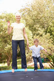 Grandmother And Grandson Jumping On Trampoline In Royalty Free Stock Photos