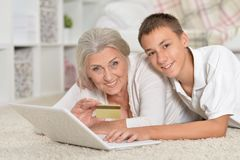 Grandmother and grandson using laptop, online shopping concept. Grandmother and grandson lying on floor and using laptop, online shopping concept Stock Photography