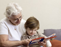 Grandmother and grandson reading book Stock Photography