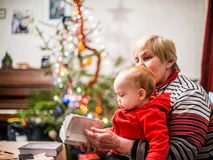 Grandmother and grandson reading a book. Grandmother with baby boy, happy love moment together in Christmas day Stock Photo